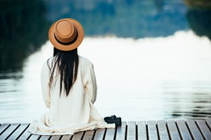 Lonely woman sitting on the waterfront raft